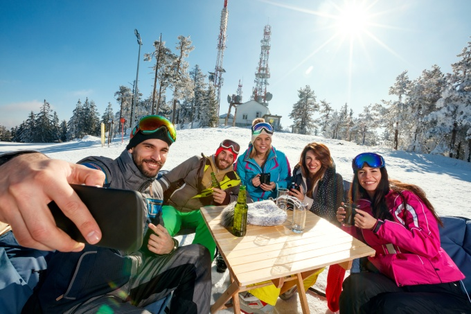 group of friends laughing and enjoying in drink at ski resort